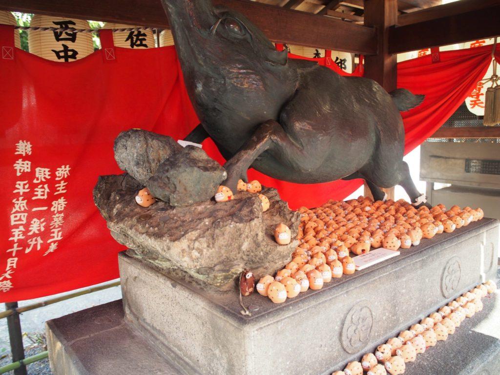 お堂のイノシシの像の足元にはたくさんの猪のお守りが