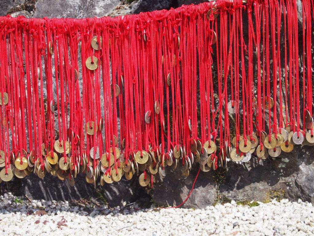 夫婦岩に五円玉をつけた赤い糸を結んで良縁祈願