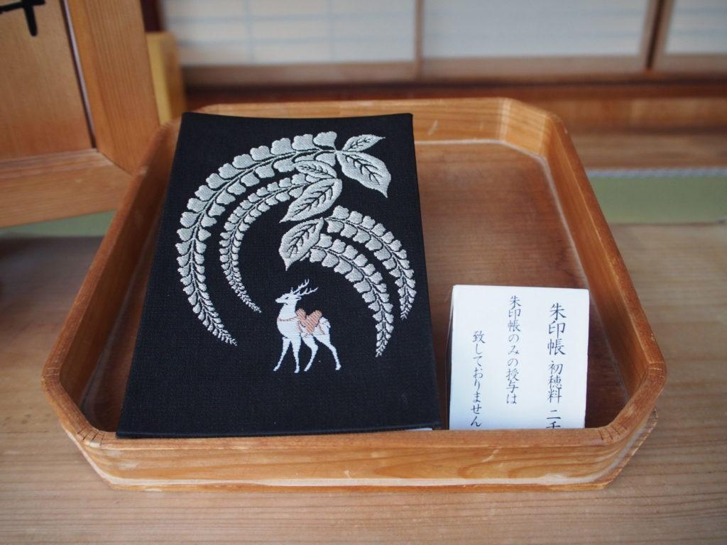 西院春日神社の御朱印帳、紺地に神鹿と六尺藤の文様入り
