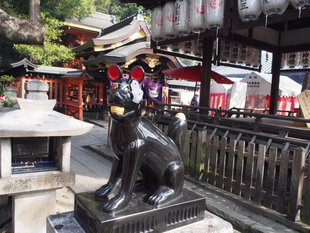 満足稲荷神社のおかめのお面を付けたツネ松