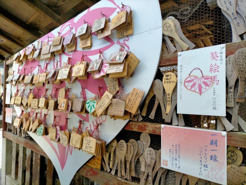 松尾大社の相生の松。ハート型の絵馬掛けにピンク色で葵が描かれた絵馬掛け所